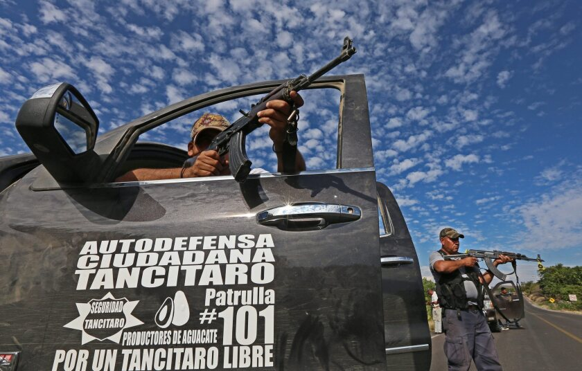 Members of a self-defense group hold a position on a road near the town of Nueva Italia, east of the key city of Apatzingan in the Mexican state of Michoacan.