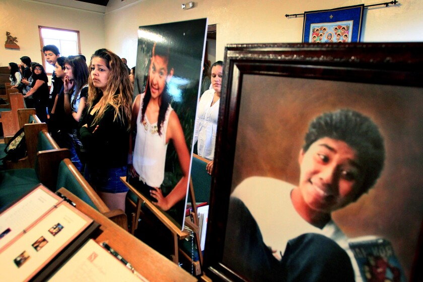 In this March 2013 photo, mourners attended a combined funeral for teenager murder victims Melanie Virgen and Edgar Sanchez at the San Luis Rey Mission Parish Chapel- Photos of the two were posted near the chapel entrance. Melanie's photo is at left, Edgar's is at right.