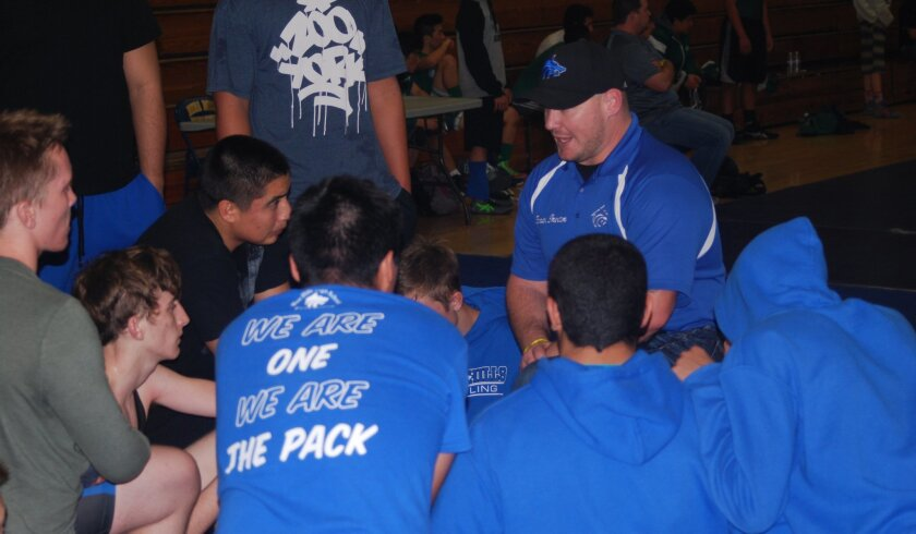 West Hills wrestling coach Michael Proctor confers with his team.