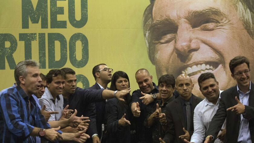 Recently elected lawmakers pose in front of an image of right-wing presidential candidate Jair Bolsonaro.