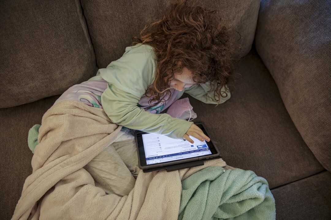 Lounging on the couch, Madelynn Singer uses her tablet at home in Porter Ranch.