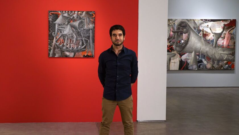 """Italian artist Siro Cugusi with his paintings """"H #5"""" (left) and """"A #4"""" at Lux Art Institute, where he is in residence through Feb. 18. His art will be on display through March 18."""