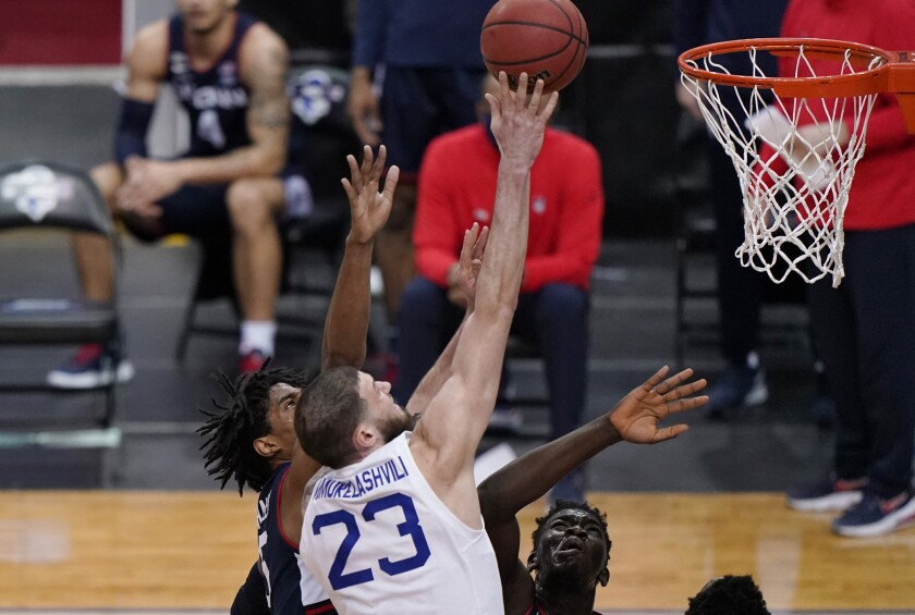 Connecticut forwards Isaiah Whaley (5) and Adama Sanogo defend against Seton Hall forward Sandro Mamukelashvili (23) during the first half of an NCAA college basketball game Wednesday, March 3, 2021, in Newark, N.J. (AP Photo/Kathy Willens)