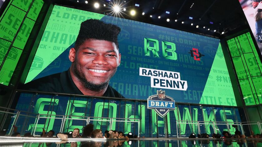A video board displays an image of Rashaad Penny of San Diego State after he was picked #27 overall by the Seahawks during the first round of the 2018 NFL Draft at AT&T Stadium on Thursday.