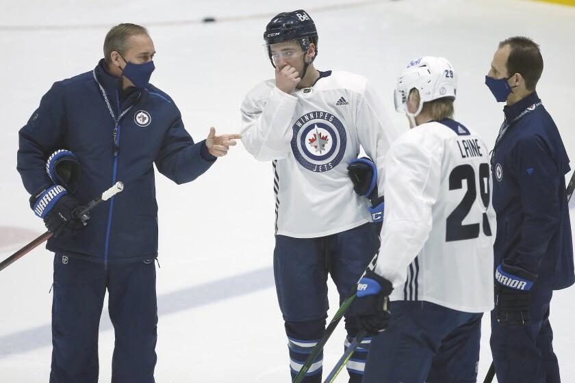 Winnipeg Jets head coach Paul Maurice, left, talks to Neal Pionk (4) and Patrik Laine (29) during their NHL hockey training camp practice in Winnipeg, Manitoba, Wednesday, Jan. 6, 2021. (John Woods/The Canadian Press via AP)