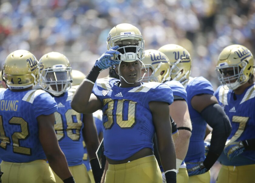 FILE - In this Sept. 5, 2015, file photo, UCLA linebacker Myles Jack, center, looks away during the first half of an NCAA college football game against Virginia at the Rose Bowl in Pasadena, Calif. Jack, No. 9 UCLA's versatile linebacker and running back, will miss the rest of the season due to a k