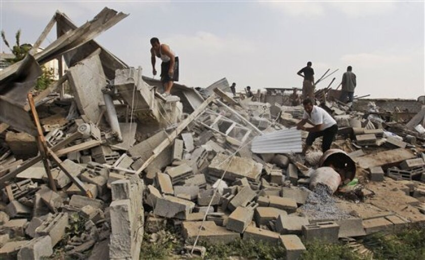 Palestinians inspect the damage at a metal workshop, following an Israeli airstrike in Gaza City, Saturday, Oct. 3 , 2009. The Israeli army says it carried out airstrikes on a weapons workshop east of Gaza City and two weapons smuggling tunnels under the Gaza-Egypt border. (AP Photo/Hatem Moussa)