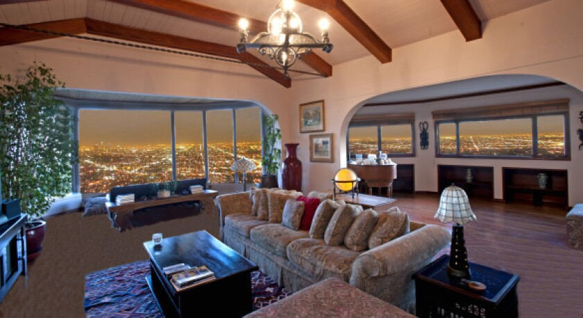 Large picture windows in a Hollywood Hills home formerly owned by Ginger Rogers and Lew Ayres take in the city lights.