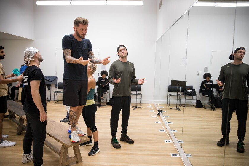 "Choreographer Travis Wall, on a bench, with actor Ryan Vasquez and the cast of ""The Wrong Man"""