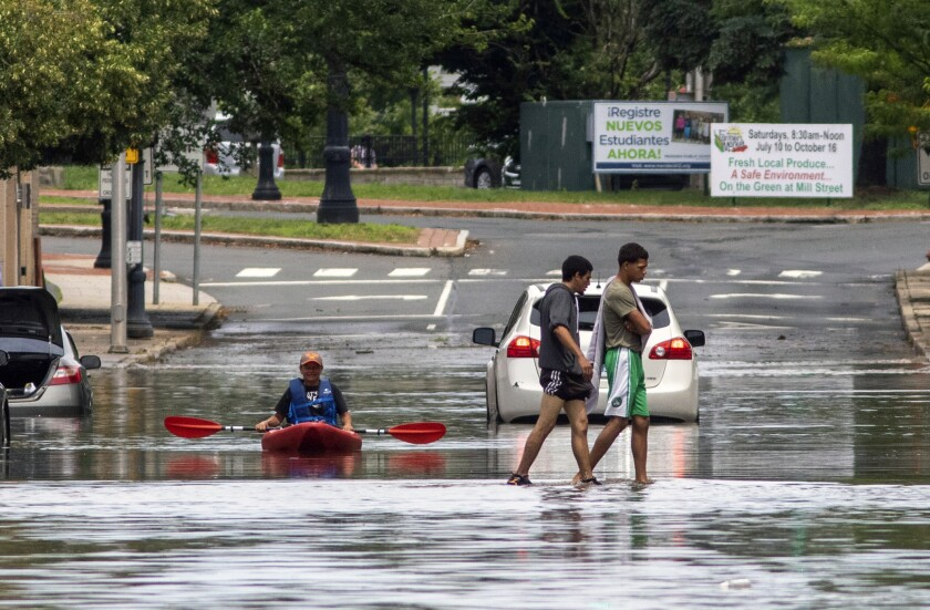 Pedestrians walk across Hanover St as a kayaker floats in the water after Tropical Storm Elsa moved through the state Friday, July 9, 2021 in Meriden, Conn. The fast-moving storm Elsa lashed New York City and New England with heavy rain and high winds Friday, flooding streets, toppling trees and hindering some rail service. (Aaron Flaum/Record-Journal via AP)