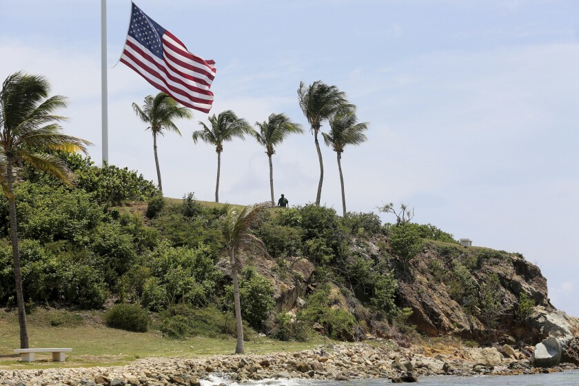 A man stands near a U.S. flag at half staff on Little St. James Island, a property owned by financier Jeffrey Epstein, on Wednesday.
