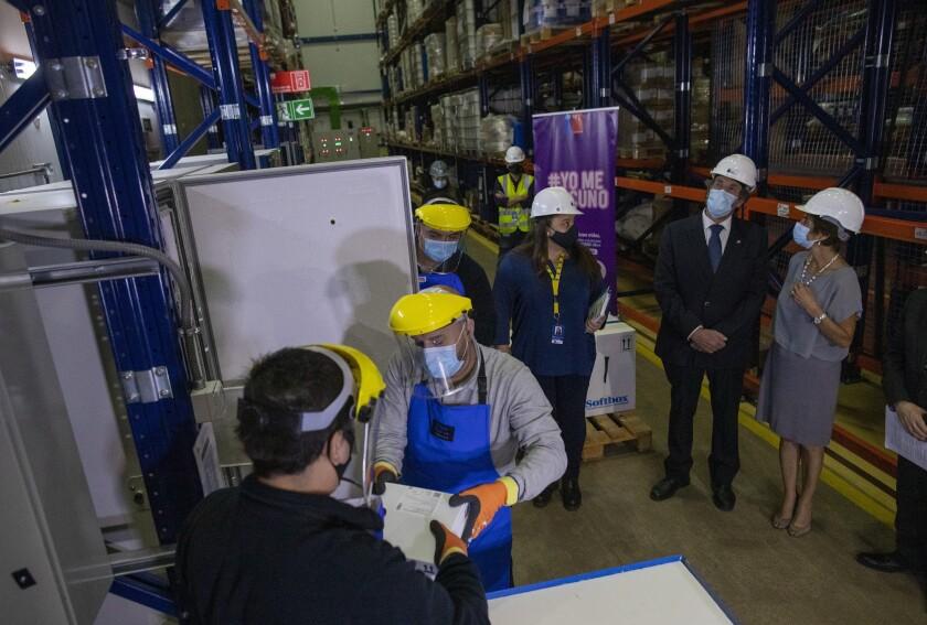 Trabajadores almacenan dosis de la vacuna Pfizer para COVID-19 en un congelador e