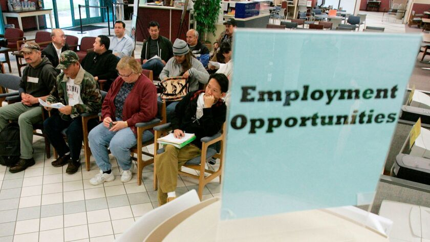 ** FILE ** In this Jan. 23, 2009, file photo people wait to talk to unemployment benefits staff at a