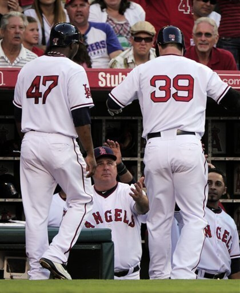 Los Angeles Angels' Russell Branyan, right, and Howard Kendrick is congratulated by manager Mike Scioscia, center, after Branyan hit a two-run home run during the seventh inning of their interleague baseball game, Sunday, July 3, 2011, in Anaheim, Calif. (AP Photo/Mark J. Terrill)