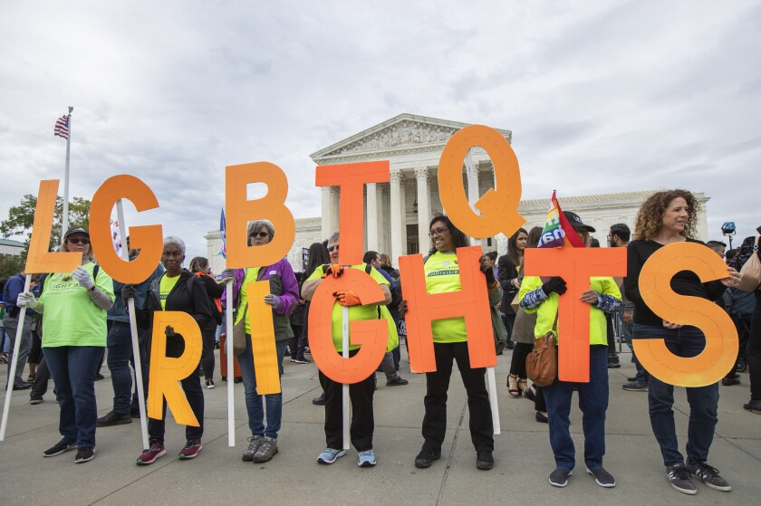 """People in matching T-shirts stand amid a crowd, holding letters that form the words """"LGBTQ rights."""""""