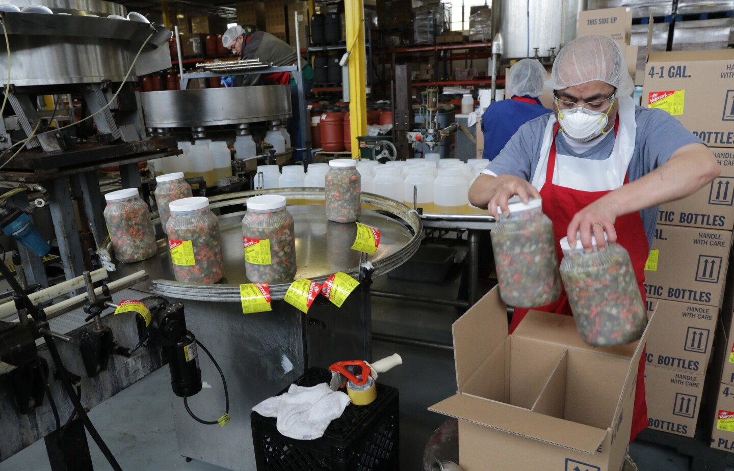 V. Formusa employees package galloons of giardiniera at the company plant on March 27, 2018. The Des Plaines-based Italian foods manufacturer and distributor wants to see tariffs removed on imported pepperoncini.