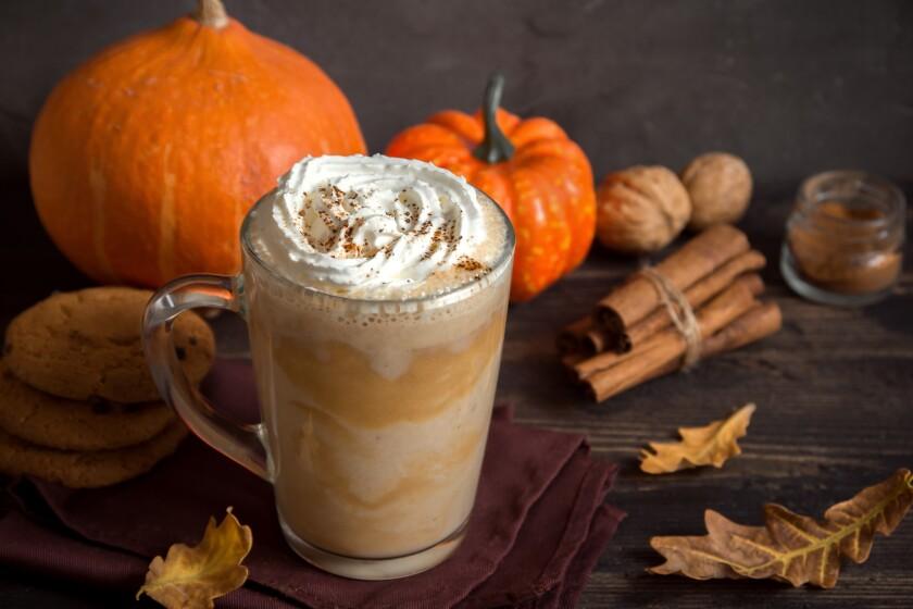 Latte on a table next to cinnamon sticks and mini pumpkins