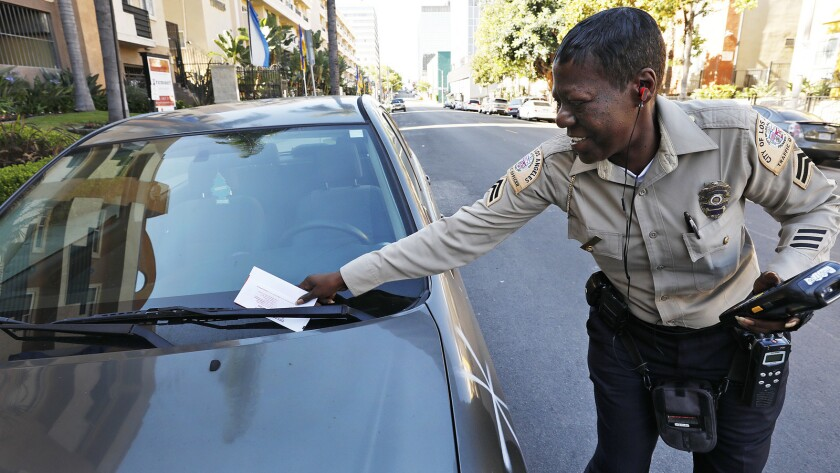 LOS ANGELES, CA - MAY 22, 2019 - City of Los Angeles Traffic Officer Rodgers places a parking violat