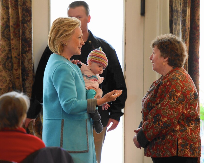 Hillary Rodham Clinton holds 6-month-old Molly Morse while speaking with Marsha Dubois, owner of Kristin's Bistro & Bakery, in Keene, N.H., on April 20. Clinton didn't embrace such displays during her last run for president.