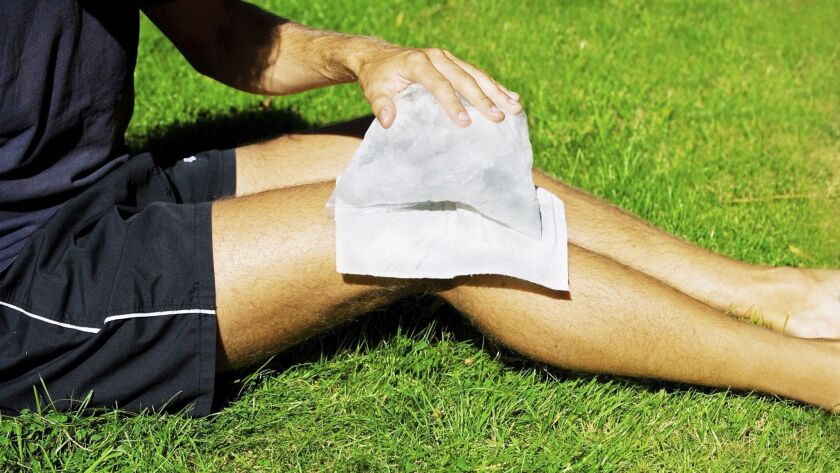 A man puts ice on his knee.