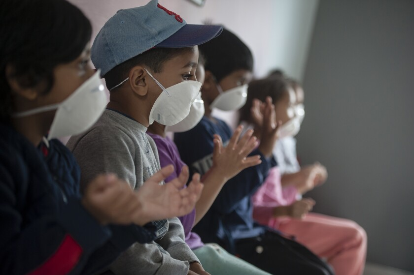 Learners wear masks as they sanitise their hans at a pre-school in Lenasia, Johannesburg, Tuesday, March 17, 2020, on the day schools closed in a bid to control the spread of coronavirus. For most people the virus causes only mild or moderate symptoms but for others is can cause more severe illness, especially in older adults and people with existing health problems. (AP Photo/Shiraaz Mohamed)