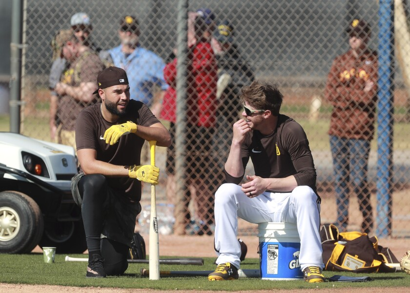 While fans watch from behind a fence, the Padres' Wil Myers, right, and Eric Hosmer talk as they wait to take their turn during batting practice on Saturday.