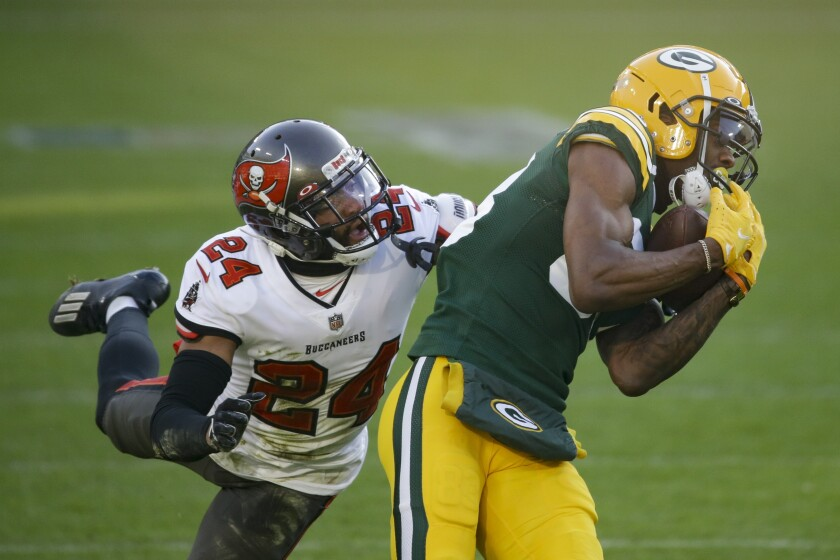 Green Bay Packers' Marquez Valdes-Scantling pulls in a 50-yard touchdown pass against Tampa Bay Buccaneers' Carlton Davis during the first half of the NFC championship NFL football game in Green Bay, Wis., Sunday, Jan. 24, 2021. (AP Photo/Mike Roemer)
