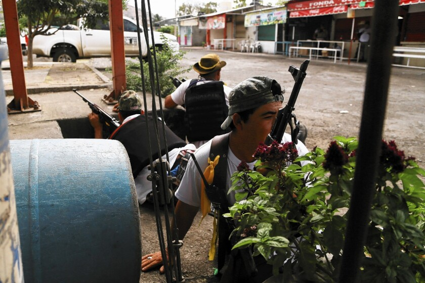 Members of a peasant group battling a drug cartel take their positions after arriving in the town of Nueva Italia in Mexico's Michoacan state. The federal government has called on such groups to disarm and go home.