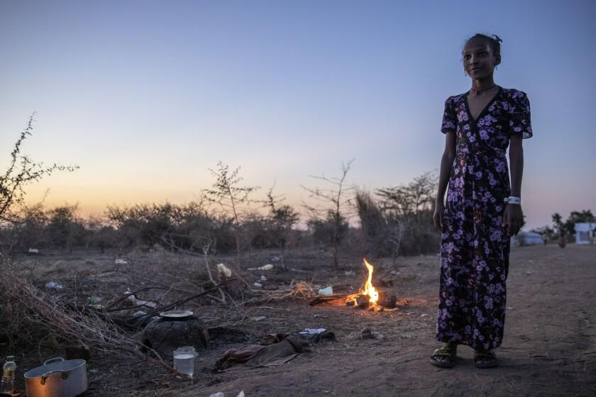 Una joven tigray, que huyó del conflicto en la región etíope de Tigray, mira a mujeres que cocinan delante de su refugio en el campo de refugiados Umm Rakouba, en Qadarif, en el este de Sudán, el 25 de noviembre de 2020. (AP Foto/Nariman El-Mofty)