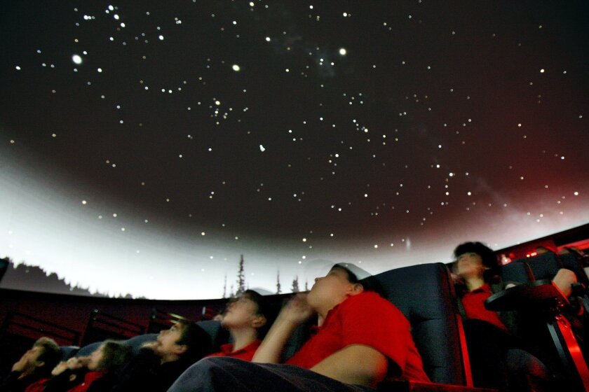 Ryan West (center), a sixth-grader from Applied Scholastics Academy in San Marcos, and other students look at the night sky projected onto a domed screen at the Palomar College planetarium on Tuesday.