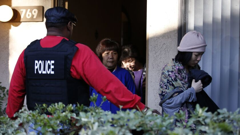 "Federal agents escort residents from an apartment in Rowland Heights during a 2015 raid on an alleged ""birth tourism"" operation. On Thursday, prosecutors charged several people in such schemes, which bring pregnant women to the U.S to give birth."