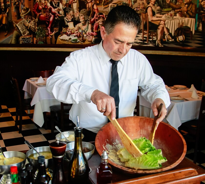 Pablo Figueroa makes the famous Caesar salad at Caesar's Restaurante Bar in Tijuana, Mexico, by mixing the dressing ingredients then gently rolling in the romaine lettuce leaves.