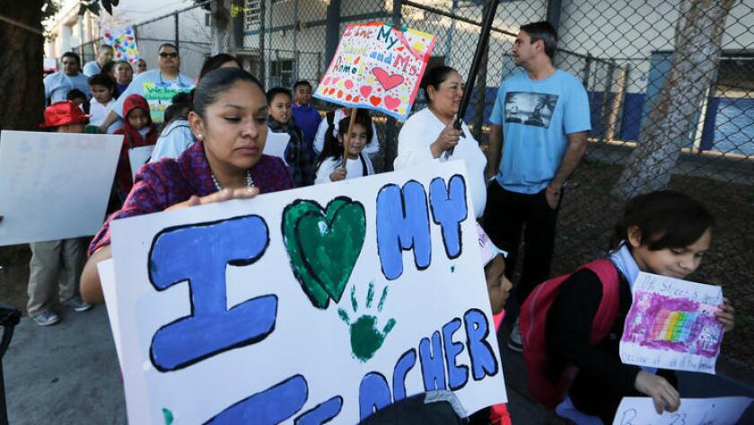 Padres, maestros y alumnos llevan carteles y pancartas durante una caminata para mostrar su lealtad a la escuela primaria 20th Street Elementary School, en Los Ángeles, el pasado 17 de febrero (Los Angeles Times).