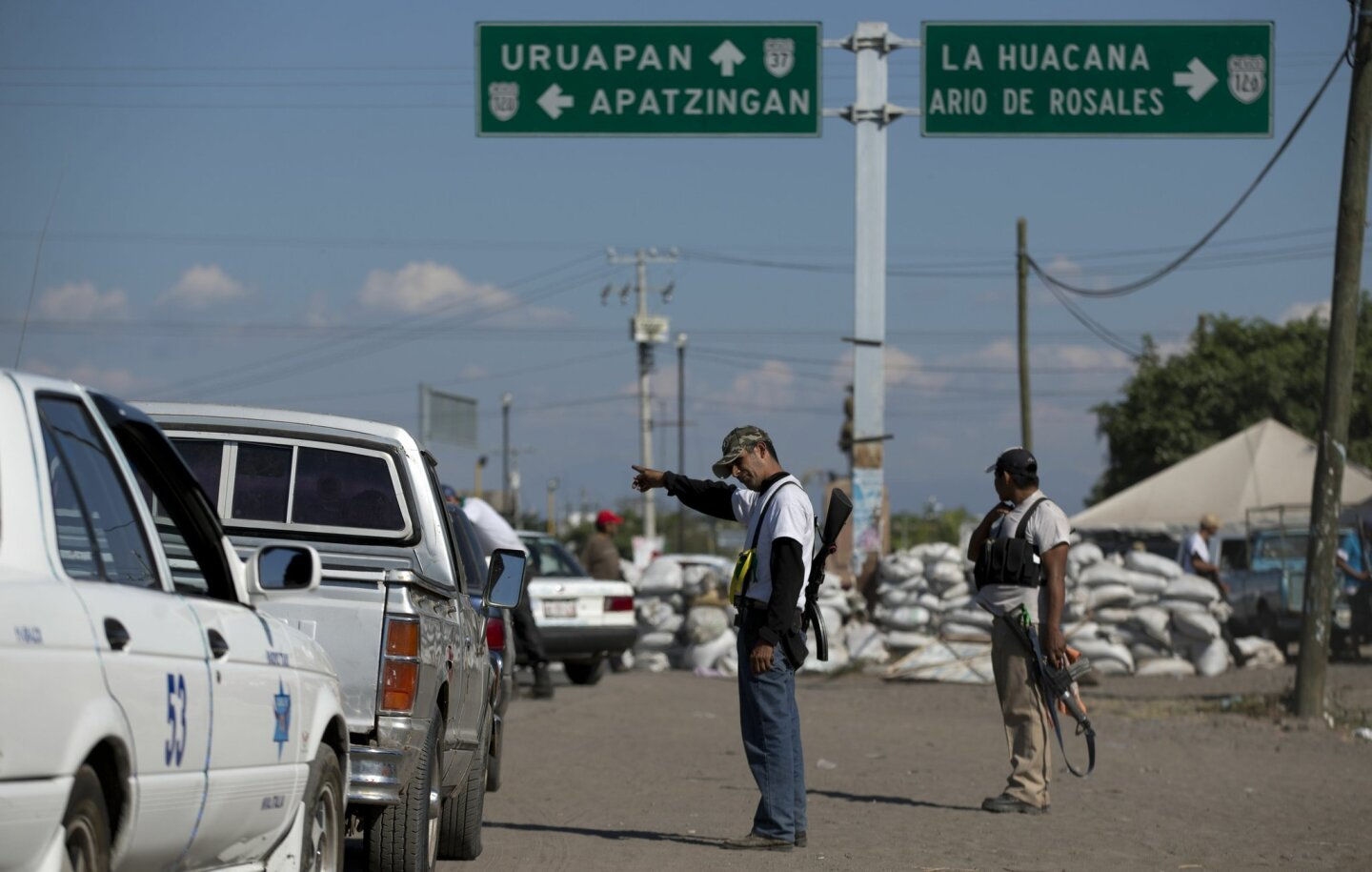 Men belonging to the Self-Defense Council of Michoacan, (CAM), inspect vehicles at a checkpoint in the entrance to the town of Nueva Italia, Mexico, Monday, Jan. 13, 2014. A day earlier the self-defenses encountered resistance as they tried to rid the town of the Knights Templar drug cartel while t