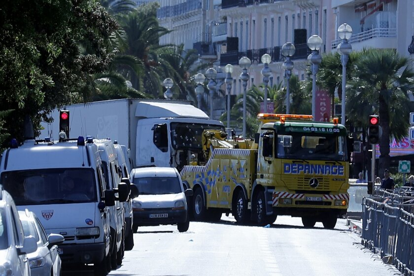 A removal truck tows the vehicle that mowed through revelers in Nice, southern France, Friday, July 15, 2016. A Tunisian living in France drove a large truck through crowds celebrating Bastille Day along Nice's beachfront, killing more than 80 people, many of them children, according to police and hospital officials. (AP Photo/Francois Mori)
