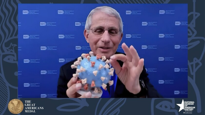 This image from video provided by Smithsonian's National Museum of American History shows Dr. Anthony Fauci, director of the National Institute of Allergy and Infectious Diseases and chief medical adviser to the president, holding his personal 3D model of the COVID-19 virus he is donating to the Smithsonian's National Museum of American History on Tuesday, March 2, 2020. Fauci presented the donation Tuesday night in a virtual ceremony to honor him with the museum's Great Americans Medal. (Smithsonian's National Museum of American History via AP)