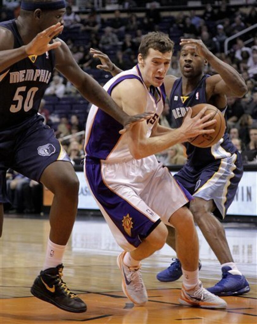 Phoenix Suns' Goran Dragic, of Slovenia, drives past Memphis Grizzlies' Zach Randolph (50) and Rudy Gay, right, during the second half of an NBA basketball game on Wednesday, Dec. 12, 2012, in Phoenix. (AP Photo/Matt York)