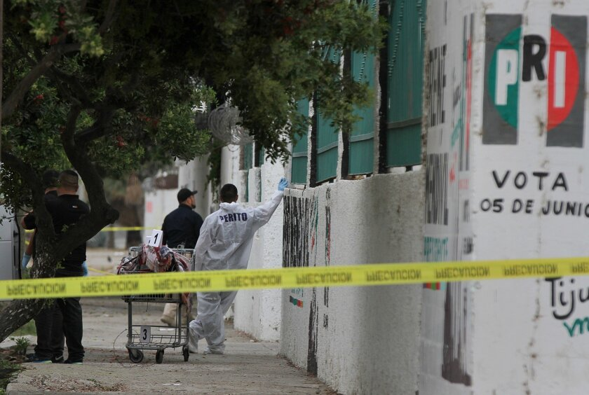 Investigators at a crime scene in Tijuana's Zona Norte, where a woman's body was found wrapped in a blanket and left in a shopping cart together with a threatening message in April 2019.
