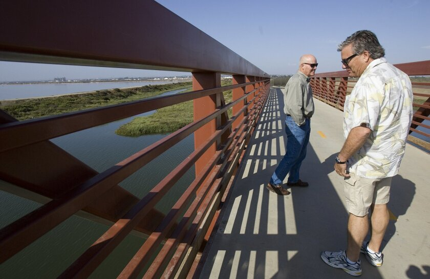 Rex Butler (right) and Terry McCaleb examine a recently completed bridge for bike riders. Butler hopes to change two warehouses into a haven for bicyclists.
