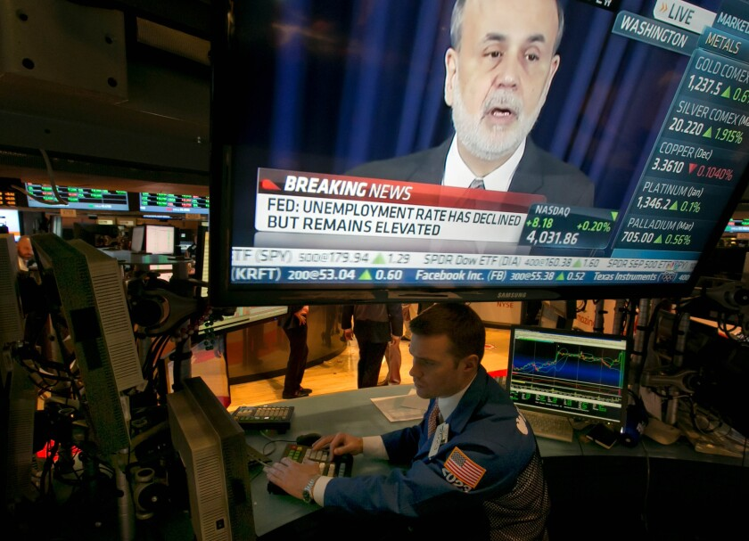 The news conference of Federal Reserve Chairman Ben Bernanke appears on a television screen at a trading post on the floor of the New York Stock Exchange on Wednesday. The Fed's Open Market Committee decided to reduce its stimulus for the U.S. economy because the job market has shown steady improvement.