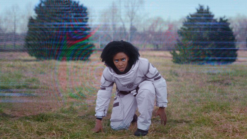 Teyonah Parris as Monica Rambeau, crouching in a space suit with glowing blue eyes