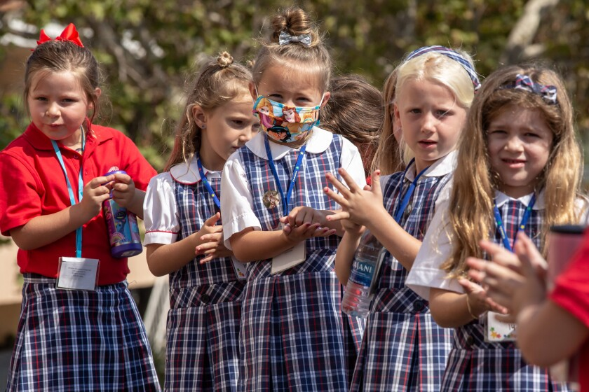 Elementary school girls rub their hands together with sanitizer at Christian Unified East on Aug. 24 in El Cajon