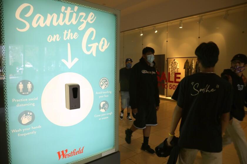 Shoppers walk past a hand sanitizer station at Westfield Santa Anita.