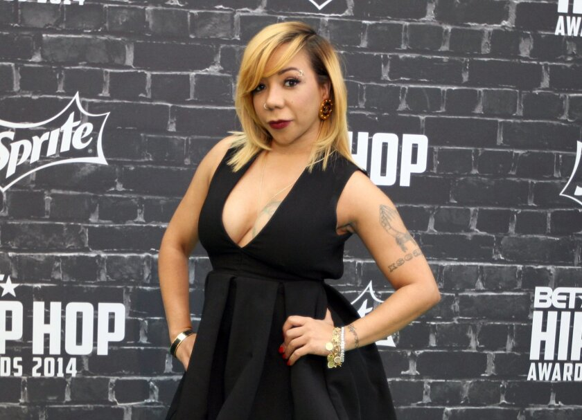 "FILE - In this Sept. 20, 2014 file photo, TV personality Takema ""Tiny"" Harris arrives at the 2014 BET Hip Hop Awards in Atlanta. Harris, the wife of rapper T.I., has the attention of skeptical eye doctors and social media haters over a procedure she underwent to permanently lighten the color of her"