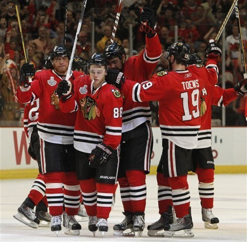 Chicago Blackhawks players celebrate after beating the Philadelphia Flyers 7-4 in Game 5 of the NHL Stanley Cup hockey finals on Sunday, June 6, 2010, in Chicago. From left are Marian Hossa, of Slovakia, Patrick Kane (88), Dustin Byfuglien, and Jonathan Toews (19). The Blackhawks lead the series 3-2. (AP Photo/Nam Y. Huh)