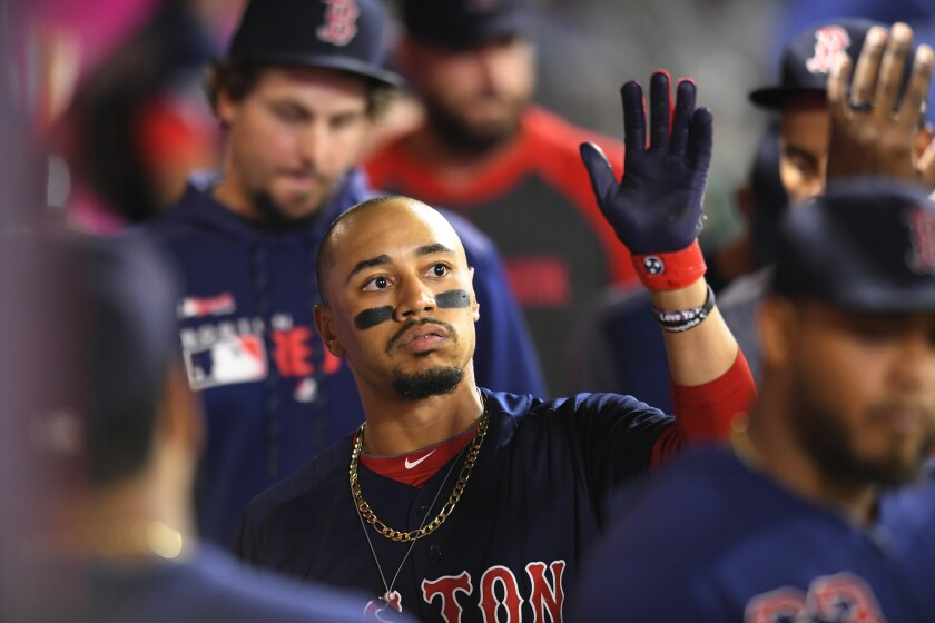 Mookie Betts celebrates with his Boston Red Sox teammates after hitting a solo home run against the Angels on Aug. 30.