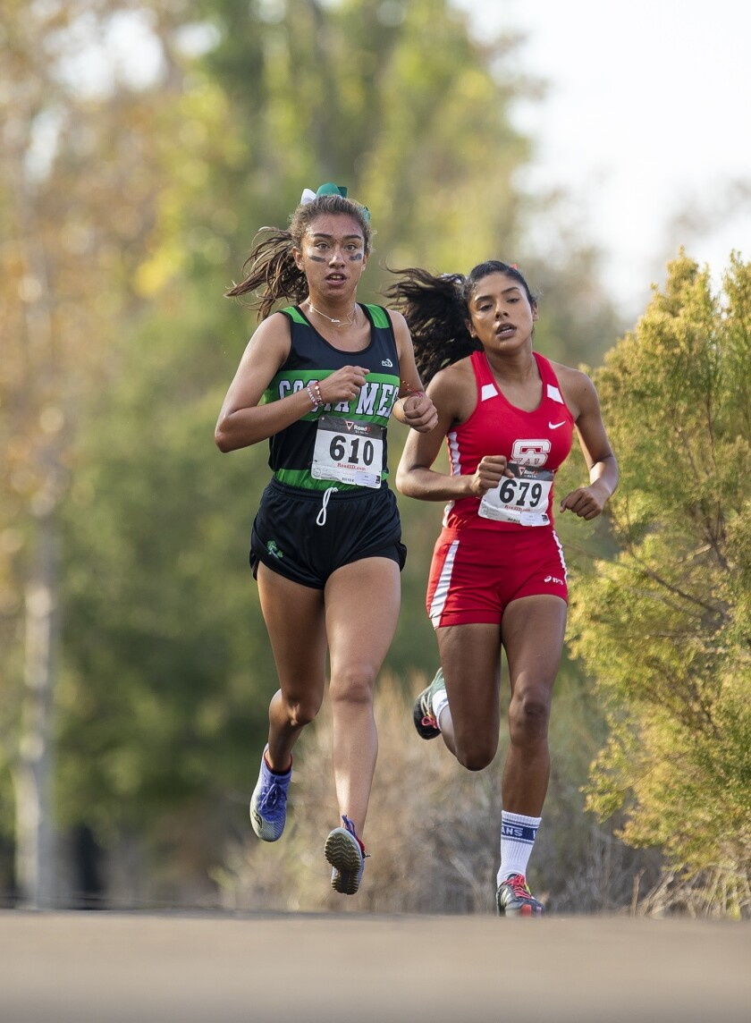 Costa Mesa's Diane Molina and Santa Ana's Maria Hernandez battle it out in the second lap during the