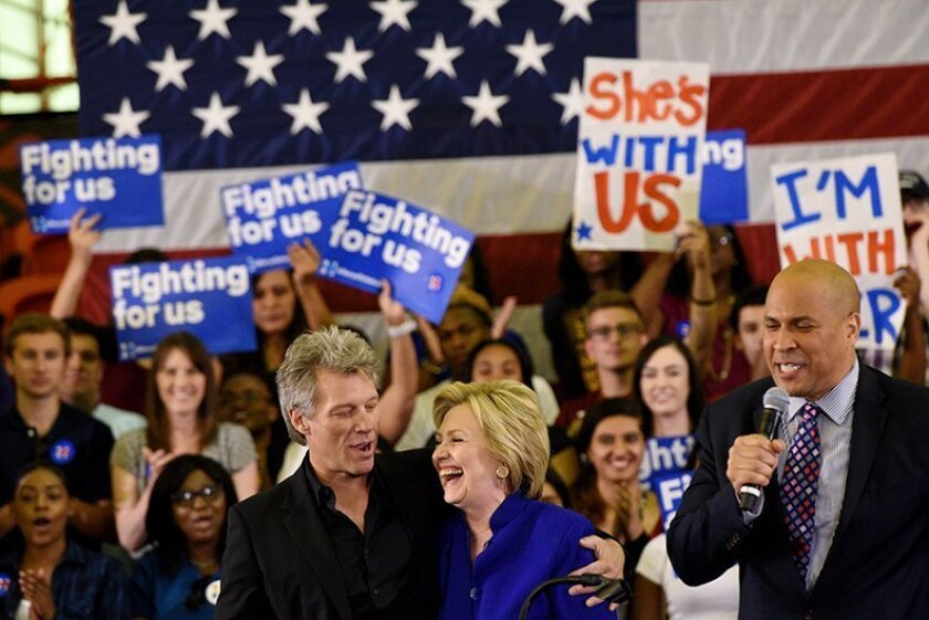 New Jersey musician, Jon Bon Jovi, from left, with Democratic presidential candidate, Hillary Clinton, after being introduced by U.S. Senator Cory Booker, NJ-D, during a campaign event held at the Golden Dome Athletic Center at Rutgers University Newark Campus in Newark, N.J., on Wednesday, June 1,