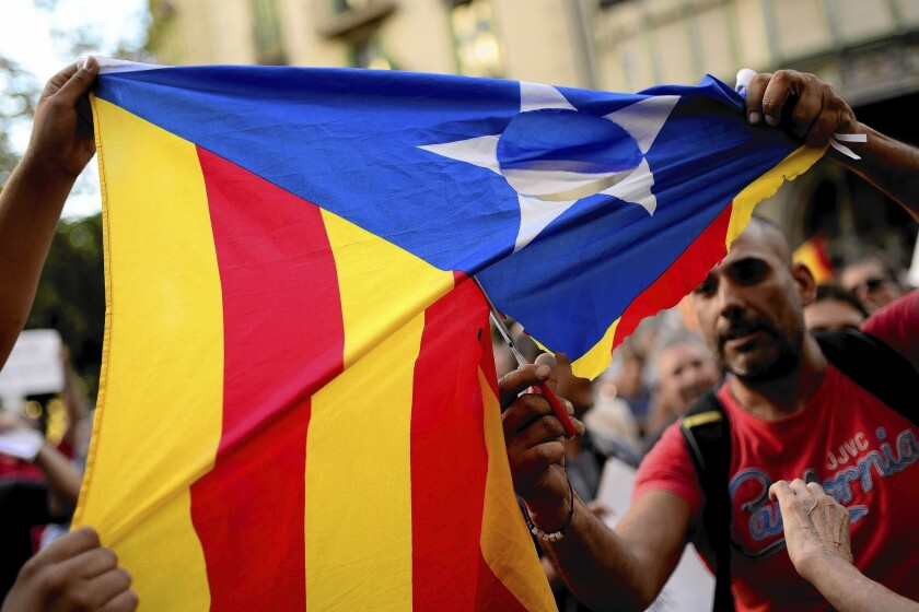 Supporters of Spanish unity cut up a flag used by those who support independence for the Catalan region during a protest in Barcelona on July 30.