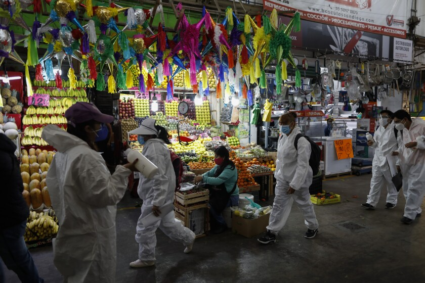 Workers wearing protective suits walk to take up positions to dispense antibacterial gel to passing shoppers and workers, inside the Central de Abastos, the capital's main market, in Mexico City, Tuesday, Dec. 8, 2020.(AP Photo/Rebecca Blackwell)